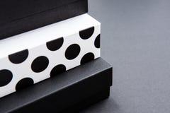 Le boîte-cadeau noir et blanc de point de polka sur une obscurité a contrasté le fond, créant une atmosphère romantique Typiqueme images stock