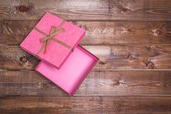 Le boîte-cadeau rose ouvert enveloppé de vintage avec sur le fond en bois peut employer la fête des mères de Saint Valentin ou cé Photographie stock libre de droits