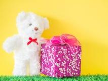 Le boîte-cadeau rose sur le verre synthétique vert et l'ours blanc jouent Photo stock