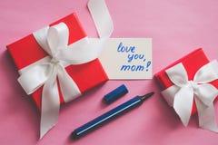 """Le boîte-cadeau rouge attaché avec un ruban blanc, les marqueurs et une carte avec une inscription """"vous aiment, maman ! """"sur un  image libre de droits"""
