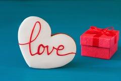 Le boîte-cadeau rouge de jour de valentines de St avec l'arc et le pain d'épice sous forme de coeur avec l'inscription aiment pou Photos libres de droits