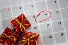 Le boîte-cadeau rouge est placé sur le calendrier et le foyer dans le quatorzième d Images stock