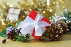 Le boîte-cadeau rouge luxueux de Noël sur le bokeh d'or allume le fond Images libres de droits
