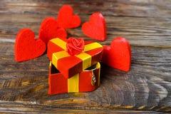 Le boîte-cadeau rouge sous forme de coeur entrebâillé, et de lui accroche un pendant sous forme de chaussure en bois avec brillan Photo libre de droits