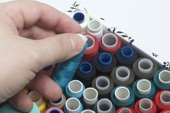 Le bobine dei fili dei colori differenti sono piegate in una scatola Una delle bobine che l'uomo prende dalla scatola Accessori p Fotografia Stock