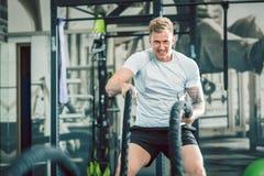 Le bodybuilder beau s'exerçant avec la bataille ropes pendant la formation fonctionnelle photo stock