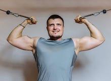 Le Bodybuilder de jeune homme travaille à son biceps dans un gymnase Images stock