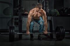 Le bodybuilder masculin soulève la barre Photographie stock libre de droits