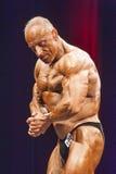 Le Bodybuilder montre la pose la plus musculaire sur l'étape dans le championnat Images libres de droits
