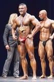 Le Bodybuilder montre sa médaille fièrement sur l'étape Photographie stock libre de droits
