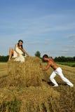 Le Bodybuilder pousse une meule de foin avec une fille sur le dessus Images libres de droits