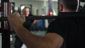Le Bodybuilder se tapit avec un barbell lourd sur ses épaules 4K MOIS lent banque de vidéos