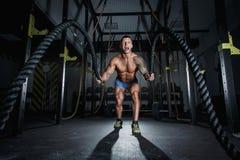 Le bodybuilder sportif d'opérateur pompe est engagé dans des cordes dans le hall du crossfit photos libres de droits
