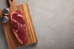 Le boeuf cru a marbré le bifteck avec les couverts blancs de vintage sur le vieux fond en pierre Un morceau de viande avec le poi Photo stock