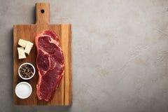 Le boeuf cru a marbré le bifteck avec les couverts blancs de vintage sur le vieux fond en pierre Un morceau de viande avec le poi Photographie stock libre de droits