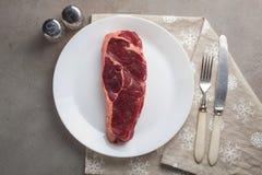 Le boeuf cru a marbré le bifteck avec les ustensiles blancs de vintage sur le vieux fond en pierre Un morceau de viande avec le p Photo stock