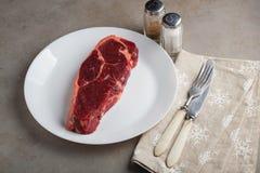 Le boeuf cru a marbré le bifteck avec les ustensiles blancs de vintage sur le vieux fond en pierre Un morceau de viande avec le p Image libre de droits