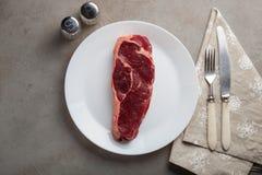 Le boeuf cru a marbré le bifteck avec les ustensiles blancs de vintage sur le vieux fond en pierre Un morceau de viande avec le p Photos libres de droits