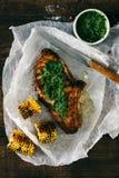 Le boeuf juteux a grillé le bifteck avec de la sauce verte sur la table en bois photo stock