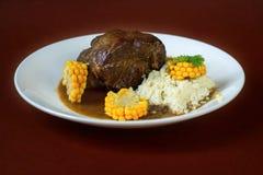 Le boeuf, le maïs et le millet de rôti se sont écaillés du plat blanc sur le fond brun Images stock