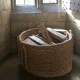 Le bois de chauffage dans un panier en osier dans le sauna Photo libre de droits