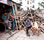 Le bois de chauffage de vente des hommes pour les bûchers funèbres indous sur la banque de la rivière le Gange Photo libre de droits