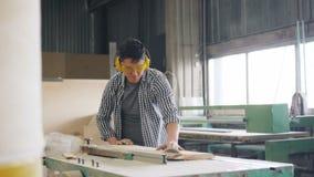 Le bois de construction sciant de charpentier avec la circulaire a vu le travail dans seul l'atelier banque de vidéos