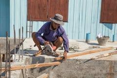 Le bois de coupe de travailleur avec la circulaire tenue dans la main a vu la machine pendant la Co Images stock