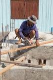 Le bois de coupe de travailleur avec la circulaire tenue dans la main a vu la machine pendant la Co Photo stock