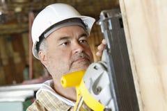 Le bois masculin sérieux de coupe de travailleur de la construction avec une puissance a vu Photo libre de droits