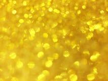 Le bokeh abstrait d'or entoure pour le fond de Noël, Li de scintillement Photos stock