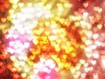 Le bokeh et l'étincelle de coeur traînent sur le fond coloré Photographie stock libre de droits