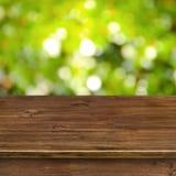 Le bokeh vert allume le fond avec la table en bois image libre de droits