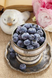 Le bol argenté de myrtilles, eustoma rose fleurit dans le backgrou Photo stock