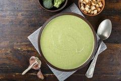 Le bol de brocoli et les pois ?cr?ment la soupe sur la table en bois photos stock