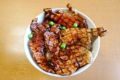 Le bol de Butadon de vue supérieure de riz a complété avec du porc coupé en tranches et le fond en bois de sauceon doux Image libre de droits