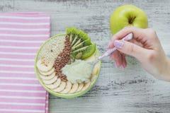 Le bol vert de smoothie a complété avec le kiwi, banane, pommes et sème f photos stock