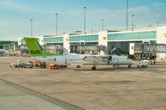 Le bombardier Q400 d'airBaltic est chargé à l'aéroport international d'Arlanda image libre de droits