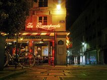 Le Bonaparte - a Paris street corner cafe at night. A bicycle parked outside a cafe close the iconic French landmark The Eiffel Tower as seen on a summery Stock Photo