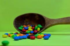 Le bonbon a assorti les chocolats multicolores, des boules de gomme dans une cuillère en bois sur un photon vert ou des comprimés photographie stock libre de droits