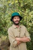 Le bondeanseende med armar som korsas i olivgrön lantgård Royaltyfri Fotografi
