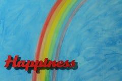 Le bonheur de mot avec un fond d'arc-en-ciel coloré et de ciel bleu Photographie stock