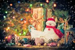 Le bonhomme de neige de carte de Noël ornemente le fond de lumières d'arbre de cadeaux Photographie stock