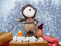 Le bonhomme de neige et le porc drôles ont trouvé des cadeaux dans la neige images libres de droits