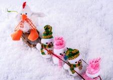Le bonhomme de neige gai sur un traîneau a tiré le coq dans la neige Photographie stock libre de droits