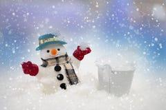 Le bonhomme de neige se tient dans les chutes de neige, le Joyeux Noël et le nouveau Y heureux images libres de droits