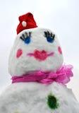 Le bonhomme de neige a vêtu dans le chapeau et l'écharpe rouges de Santa Claus Photos libres de droits