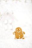 Le bonhomme en pain d'épice et la maison en bois sur Noël de fête neigent Photos stock