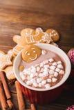 Le bonhomme en pain d'épice se baigne dans une tasse de chocolat ou de cacao avec la guimauve Bonhomme en pain d'épice dans la ta Images stock