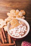 Le bonhomme en pain d'épice se baigne dans une tasse de chocolat ou de cacao avec la guimauve Bonhomme en pain d'épice dans la ta Photographie stock